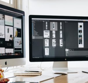2 computer screens with web design software